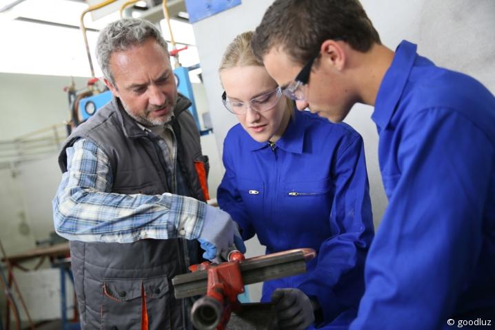 Apprentis plombiers en bleu de travail écoutant les instructions de leur maître d'apprentissage