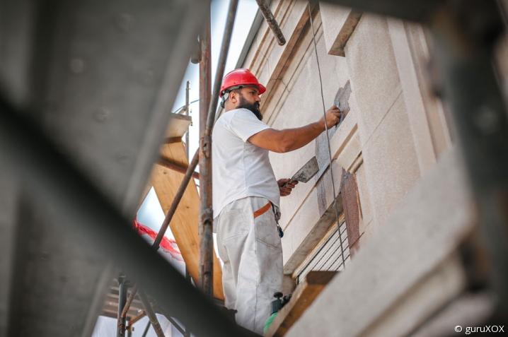 Artisan du bâtiment travaillant sur une façade