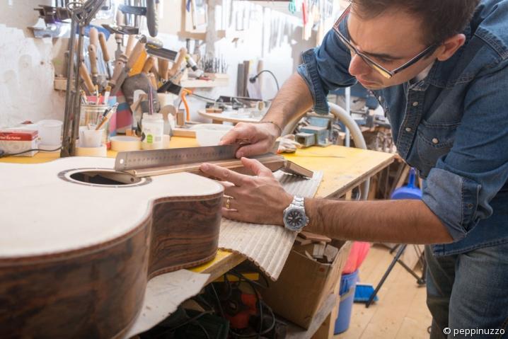 Un artisan luthier prend des mesures sur une guitare en cours de fabrication.