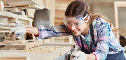 Apprentie menuisière portant des lunettes de sécurité, sciant une planche de bois